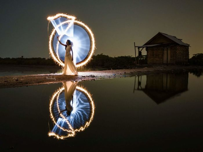 Mid adult woman making light painting while standing by lake against sky at night