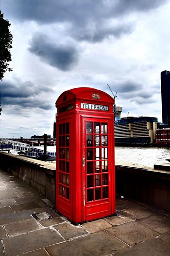 Red telephone booth by river against cloudy sky