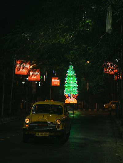 Car on illuminated street in city at night