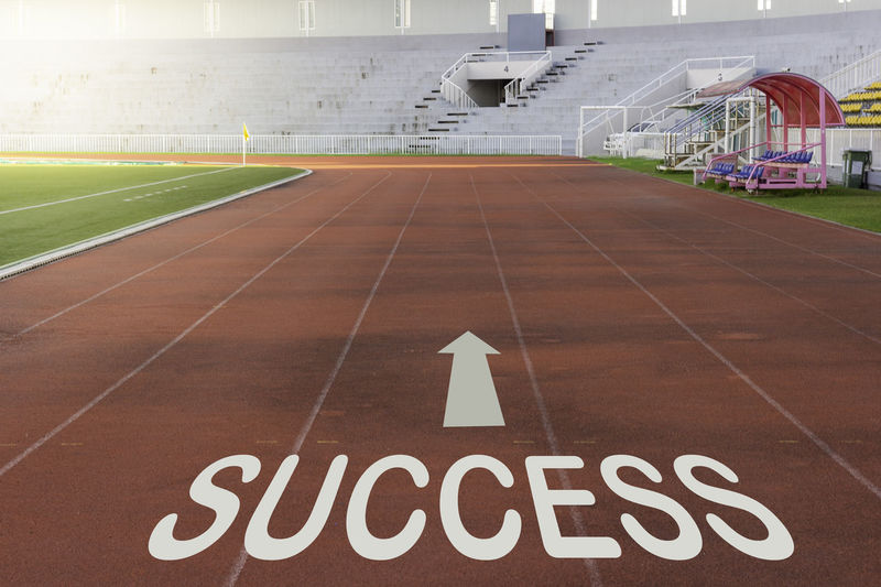 Red running track in stadium with success word Architecture Building Exterior Built Structure Communication Day Direction Empty Information Message Nature No People Number Outdoors Running Track Sign Sport Stadium Success Text Track And Field Western Script