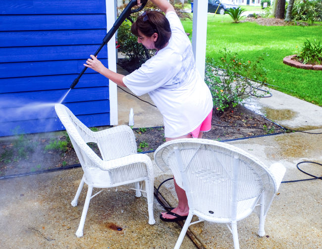 Woman pressure washing wicker chairs; Summer cleaning; porch furniture; performing in an untraditional role Cleaning PRESSURE WASHING Summer Cleaning Untraditional Role Wicker Chair Woman Adult Chair Day Full Length Holding Leisure Activity Lifestyles Nature One Person Outdoors Porch Chair Real People Seat Side View Sitting Southern Life Women Young Adult Young Women