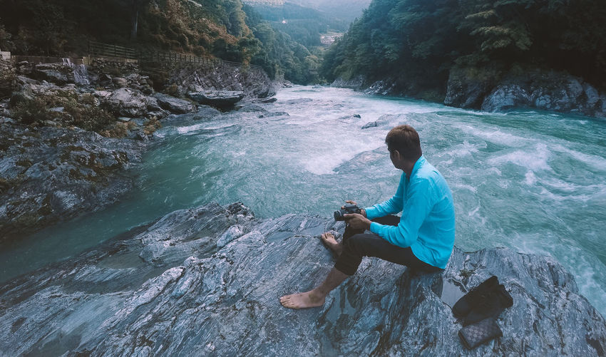 Full length of man holding camera sitting on rock by river