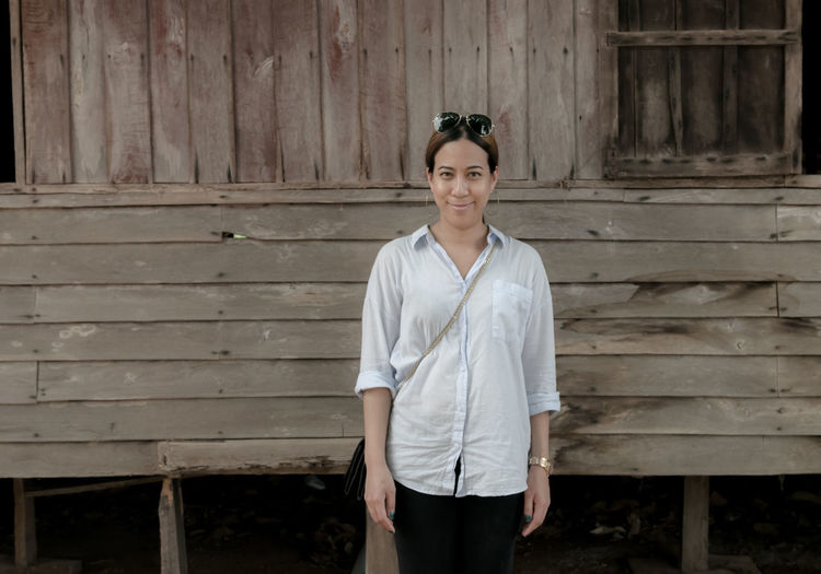 Portrait Of Mid Adult Woman Standing By Wooden House
