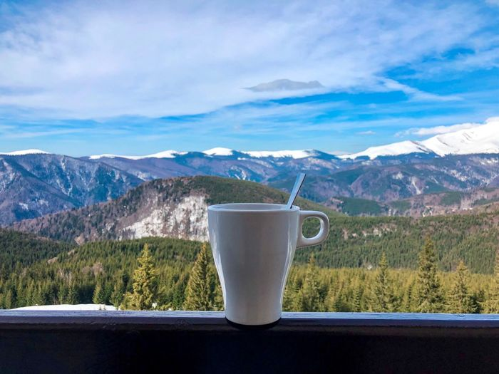 White cup placed on wooden railing on the balcony with view of snowcapped mountains Landscape View Balcony Railing Terrace Coniferous Tree Pine Tree Forest Beverage Coffee Snowcapped Mountain Mountain Drink Cup Sky Cloud - Sky Refreshment Mug Mountain Range Food And Drink Coffee Cup Snow Tranquility Beauty In Nature No People Scenics - Nature Tranquil Scene Day Nature Non-urban Scene