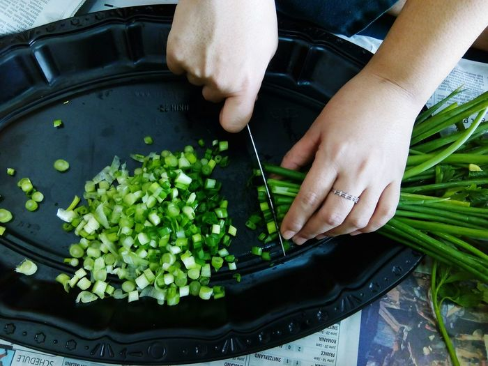 Cropped image of woman chopping spring onions in tray at home