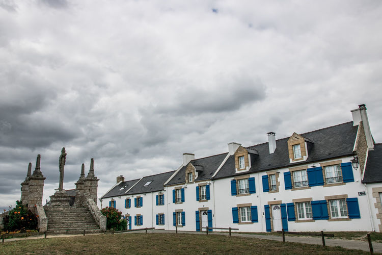 Bretagne Calvary Saint Cado Architecture Belief Building Building Exterior Built Structure Cloud - Sky Day House Island Low Angle View Nature No People Outdoors Place Of Worship Religion Residential District Row House Sky Spirituality Travel Destinations Window