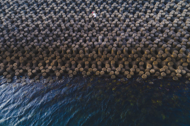 High Angle View Of Person On Tetrapods By Sea