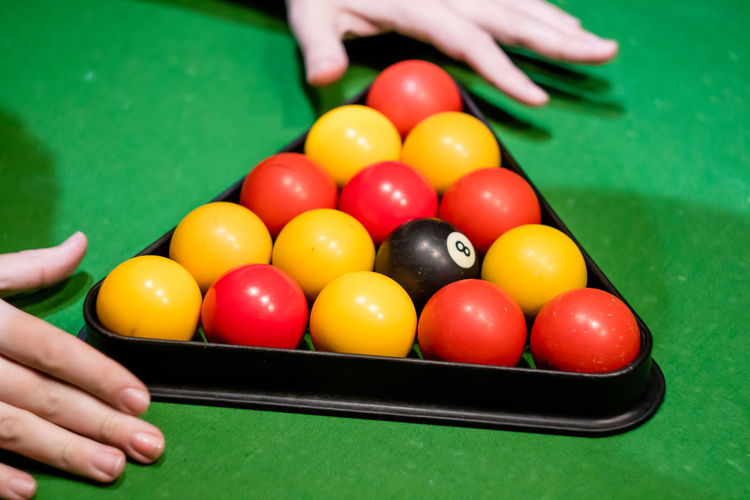 Cropped hands adjusting balls on pool table