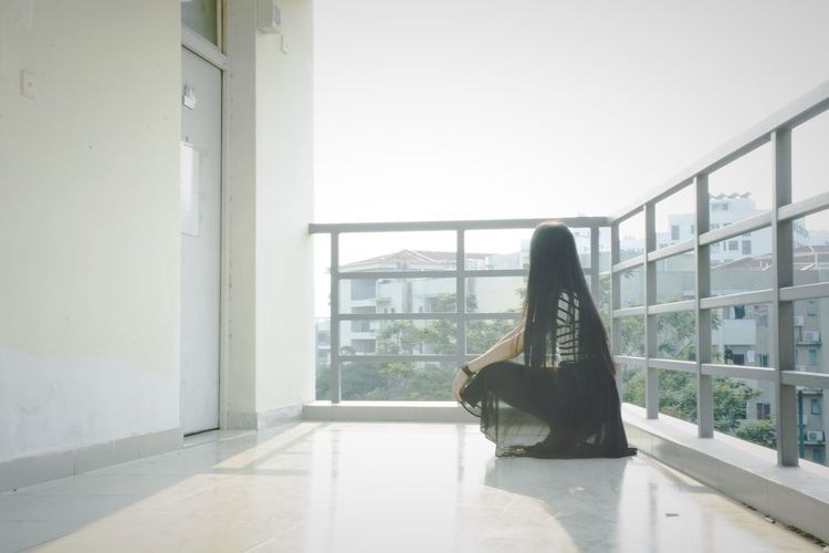 Side view of woman sitting on balcony