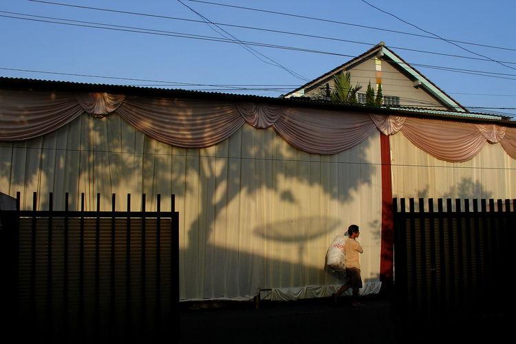 Man walking outside house against sky