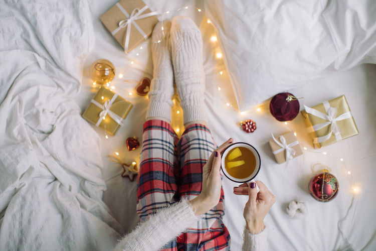 Directly above shot of woman holding coffee cup on bed