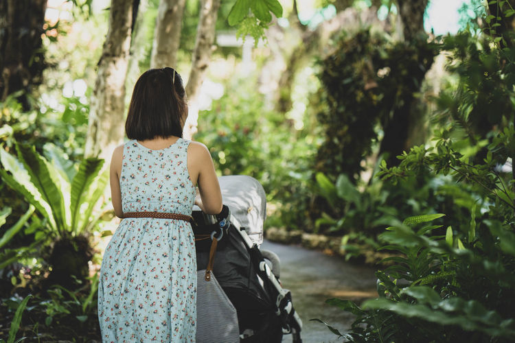 Rear view of woman with baby stroller amidst trees and plants