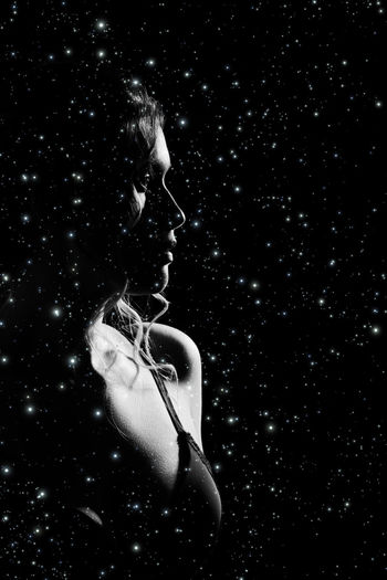 Digital composite image of woman against black background