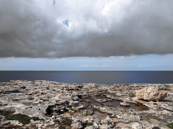 scenic view of a coastline with rock pools on the edge of a limestone beach with bright blue calm summer sea dark clouds Rock Pools Rock Coastline Idyllic Sky Water Cloud - Sky Horizon Over Water Beauty In Nature Tranquil Scene Beach Solid Sea Horizon Tranquility Rocky Coastline Outdoors Scenics - Nature Rock - Object Nature No People Day