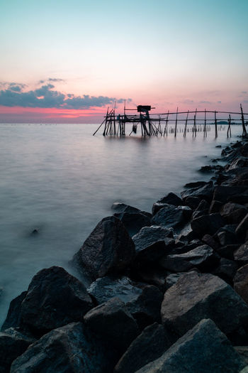 Wooden jetty at the rocky seaside during sunset. Long Exposure Vertical Orientation Water Sky Sea Sunset Rock Rock - Object Solid Beauty In Nature Tranquil Scene Scenics - Nature Tranquility Cloud - Sky Nature Pier Horizon Over Water Architecture Beach No People Horizon Outdoors Groyne Long Exposure