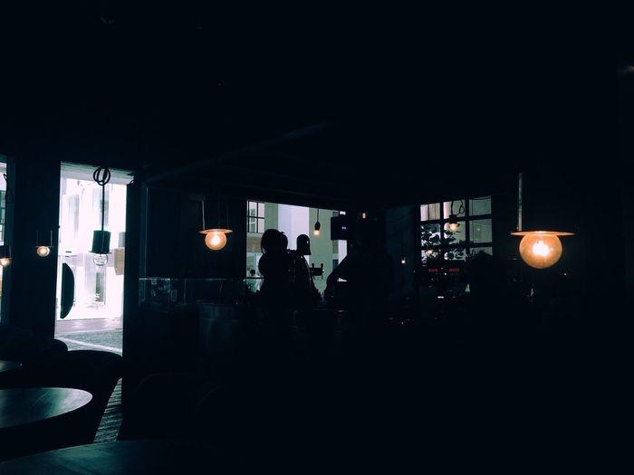 Silhouette people in illuminated room