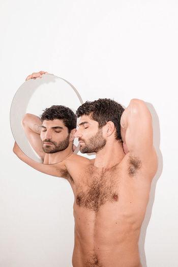 Full length of shirtless man against white background