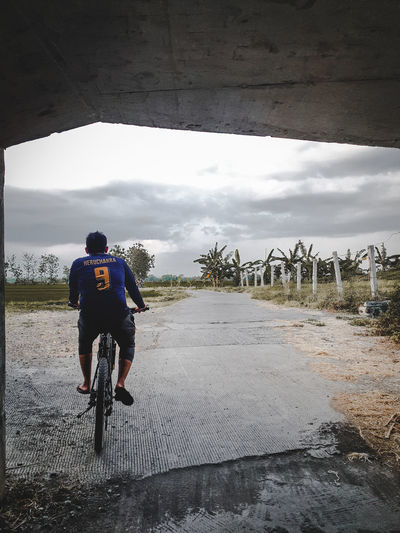 Rear view of man riding bicycle against sky