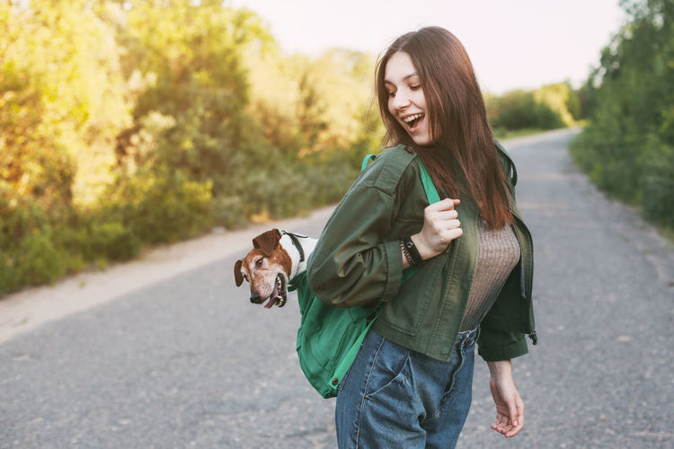 A beautiful girl is holding a green backpack on her shoulder, from which