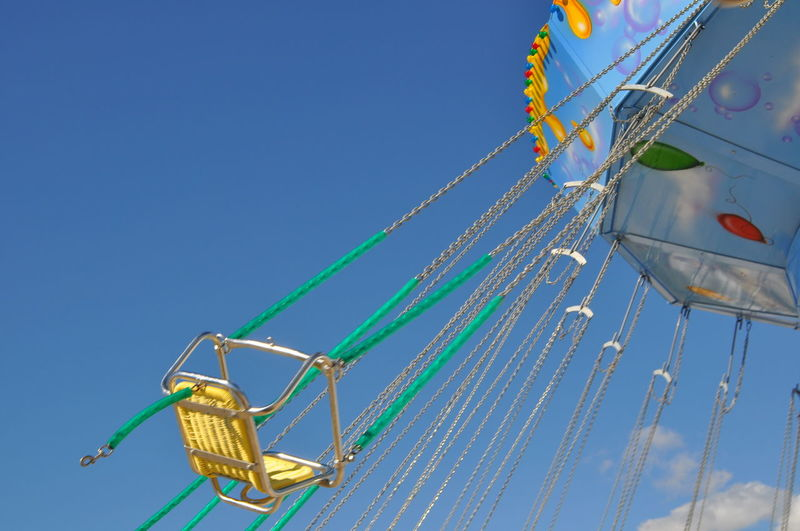 Low angle view of empty chain swing ride against sky