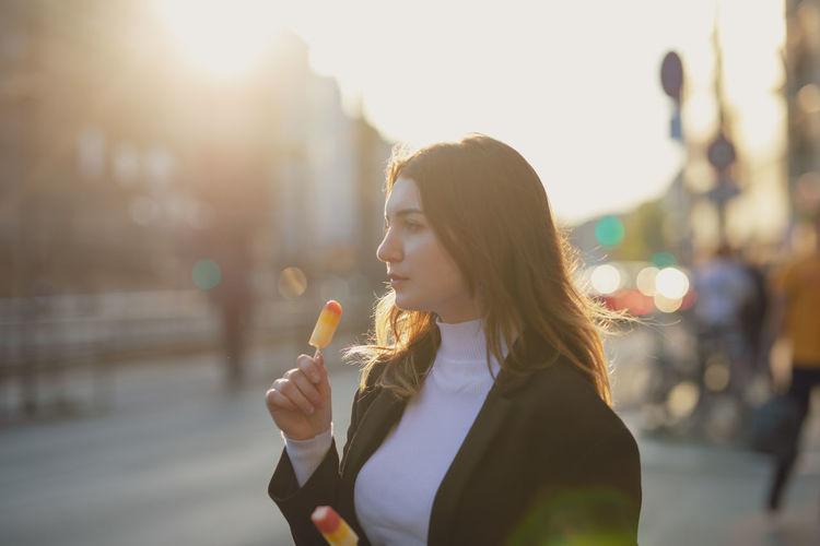 Thoughtful beautiful woman holding flavored ice in city