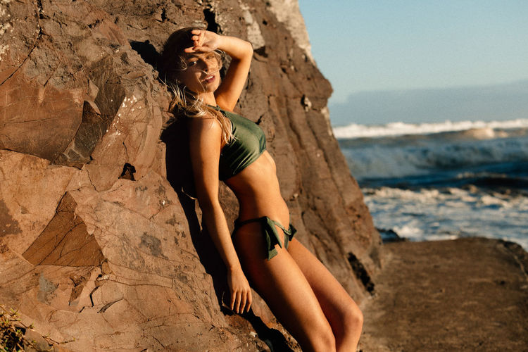 Beautiful young woman wearing bikini against rock formation at beach