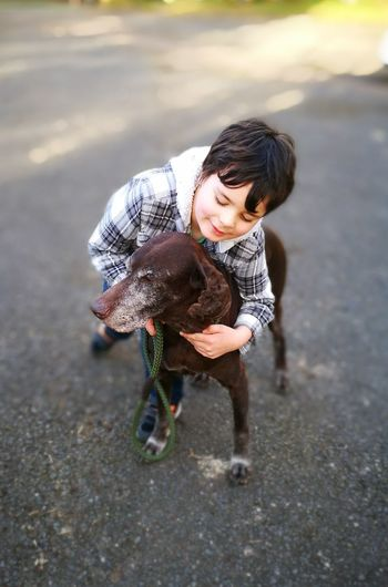 High Angle View Of Boy Playing With Dog