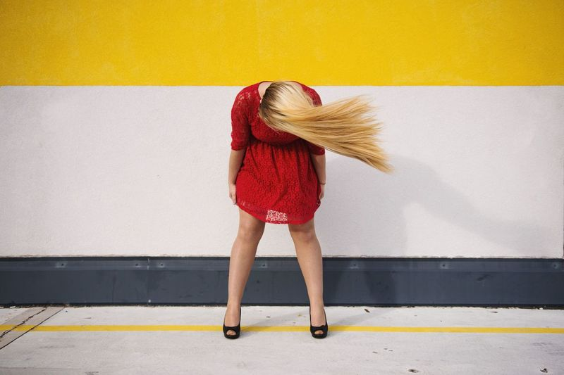 Woman Tossing Hair While Standing Against Wall