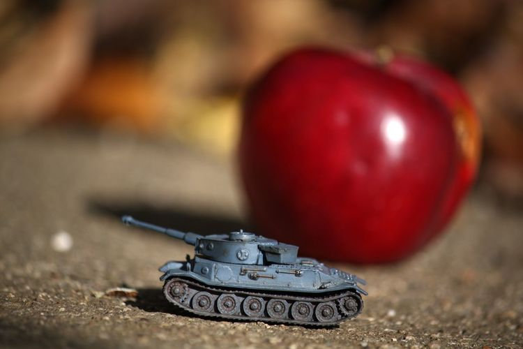 Close-up of armored tank against apple on footpath