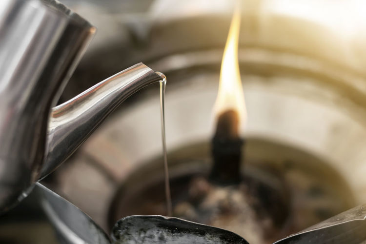 Close-up of oil pouring in burning diya