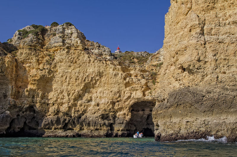 Farol Da Ponta Da Piedade/Lagos Beauty In Nature Cliff Day Eroded Formation Geology Land Lifestyles Nature Outdoors Physical Geography Real People Rock Rock - Object Rock Formation Scenics - Nature Sea Sky Solid Tranquility Water Waterfront