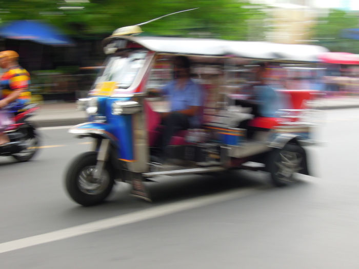 Blurred motion of people riding motorcycle on street in city
