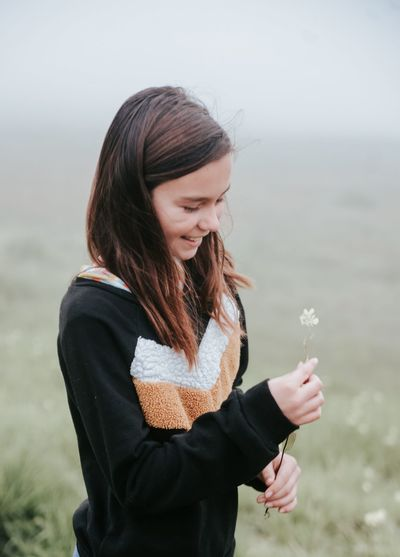 Young woman holding flower petals on land