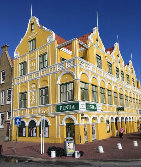 One of the many beautiful, colorful buildings In Willemstad, Curacao Historic Tropical Island Vacation Travel Travel Destinations World Heritage Site Vibrant Clear Crisp Clear Blue Sky Blue Sky Beautiful Bright Colors Bright Yellow Architecture Built Structure Arch Building Exterior Outdoors Clear Sky Day Sky No People City The Architect - 2018 EyeEm Awards