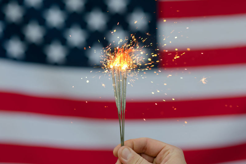 USA flag Celebration Human Hand Firework One Person Holding Motion Human Body Part Real People Sparkler Hand Red Blurred Motion Event Illuminated Long Exposure Focus On Foreground Sparks Burning Glowing Firework - Man Made Object Firework Display Finger Outdoors