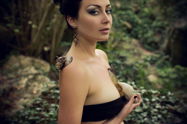Portrait of woman with snails on body in forest
