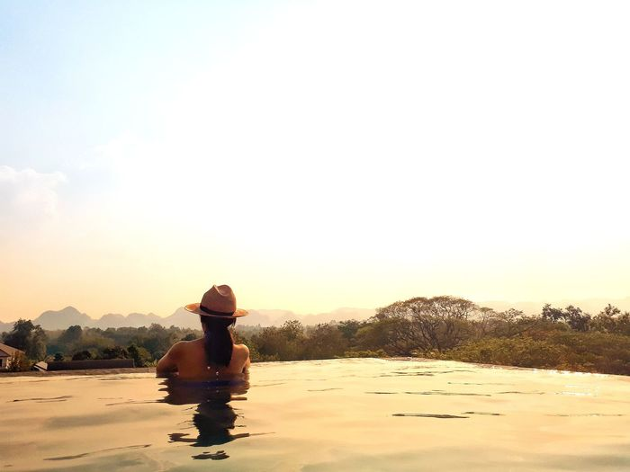 Rear view of woman looking at landscape while resting in infinity pool against sky during sunset