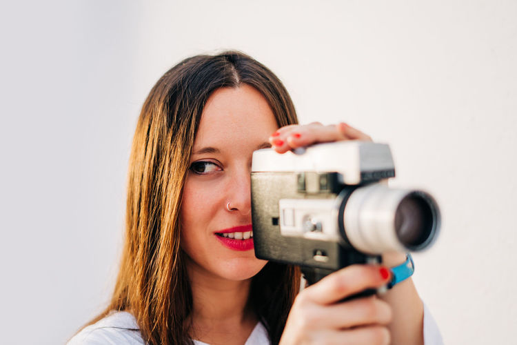 Close-up of woman looking away while holding camera