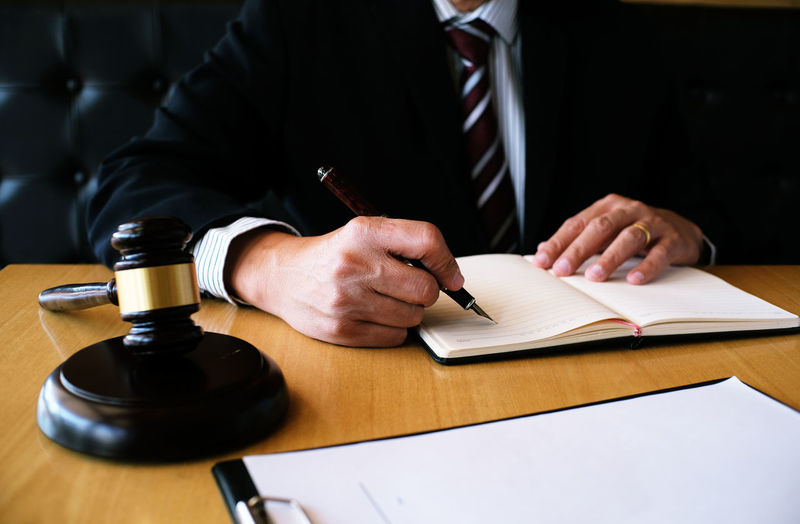 Cropped image of judge writing in book at desk