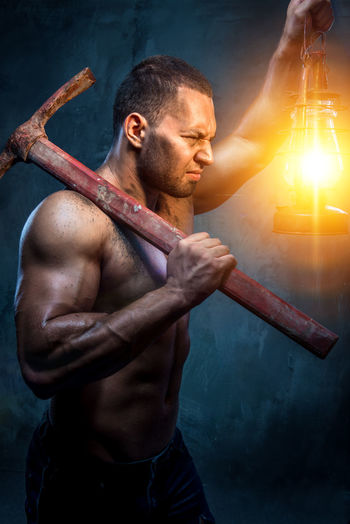 Shirtless Muscular Worker Holding Lantern And Pick Axe While Standing Against Wall