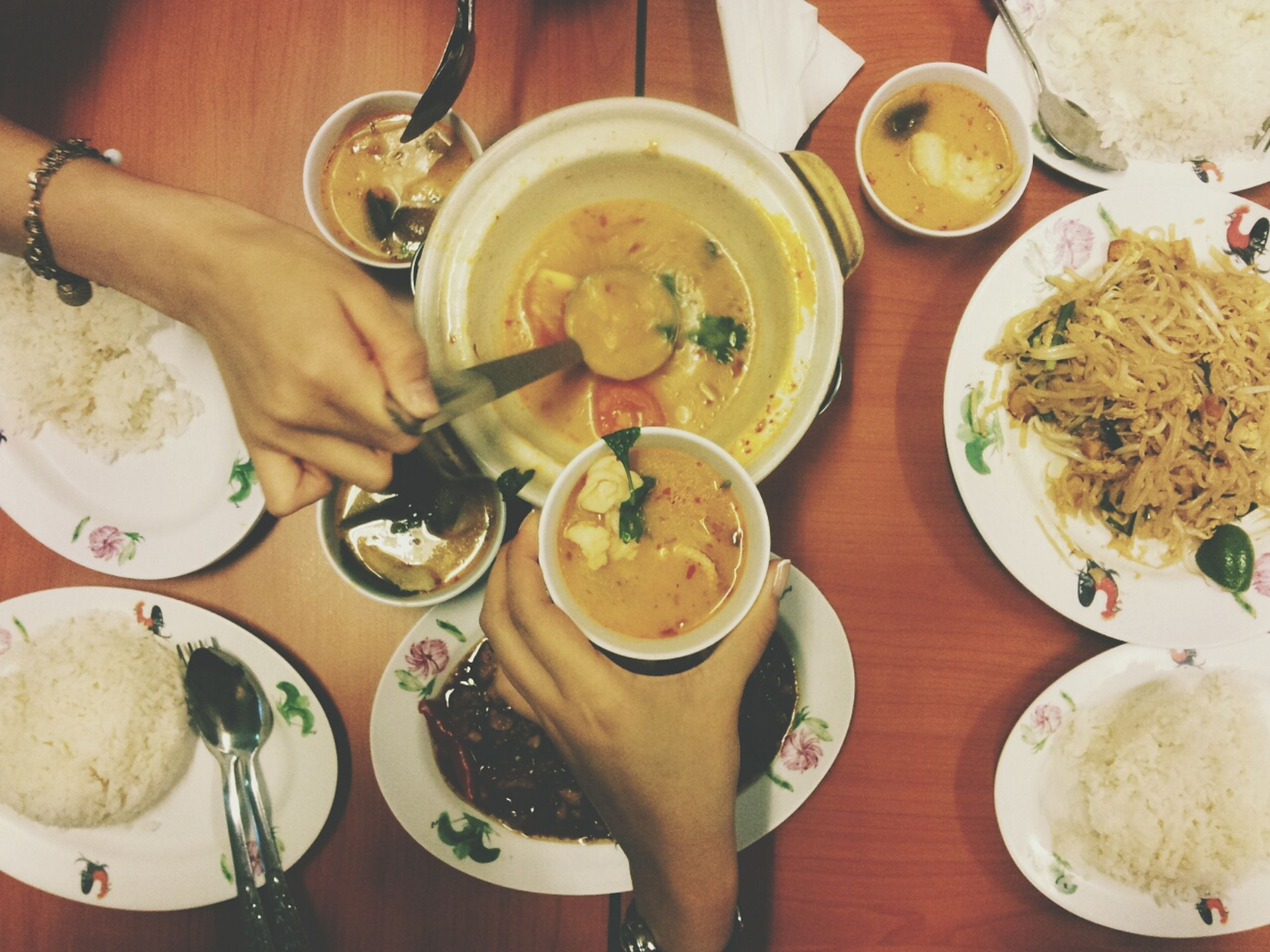 food and drink, freshness, indoors, food, table, drink, person, spoon, plate, ready-to-eat, refreshment, healthy eating, bowl, holding, high angle view, part of, coffee cup