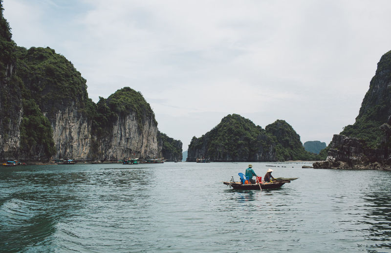 People On Boat At Halong Bay By Mountains