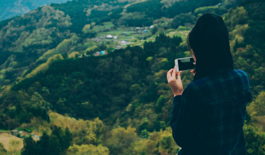Woman Photographing Lush Landscape