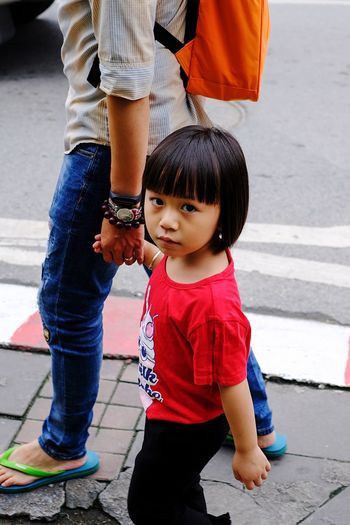 Portrait of girl walking with mother on footpath