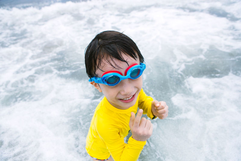 High angle view of boy enjoying in sea