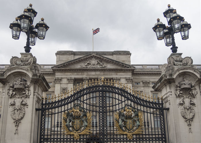London, United Kingdom - October 11, 2018; Gate of Buckingham palace with the flag as a sign the queen of England is at home Gate Buckingham Palace Flag United Kingdom London Building Exterior Low Angle View Representation Travel Destinations Building Outdoors History Architecture Palace