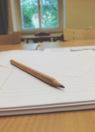 Pencil lying on sheets of paper on table