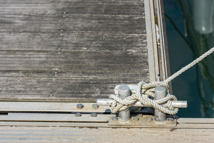 Close-up of rope tied to cleat at harbor