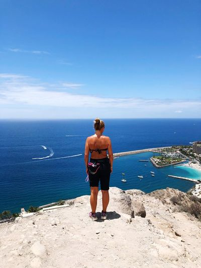 Rear view of woman standing on cliff with sea in background against blue sky
