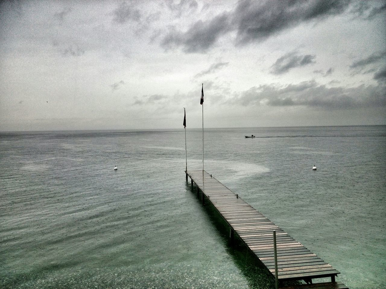 Flags On Jetty In Sea Against Sky